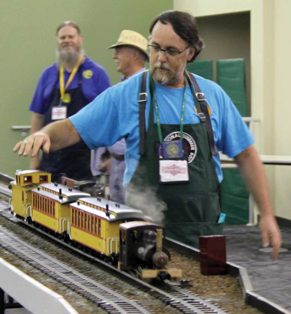 Glen Simpson is ready to provide his little consist with any help it might need; in the background, David Lindholm (left) and Doug Prescott ponder the wonderfulness of steam.