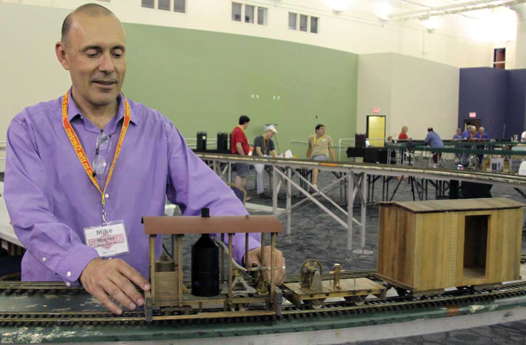 Mike Martin rerails his backwoods locomotive on the PCLS layout; the engine and the cars are all designed by Mike and scratch built.