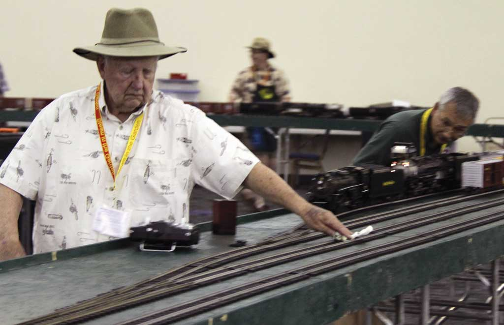 The Paso Robles layout needs frequent cleaning and Reggie Bowles is providing the elbow grease; that's Mark Kelley in the background, watching the fan on his locomotive as it fires up.